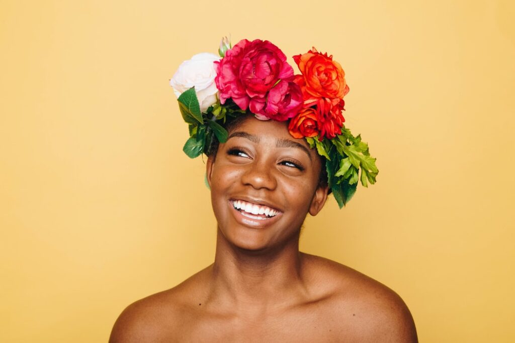 Confident black woman with flowers on her head and yellow background