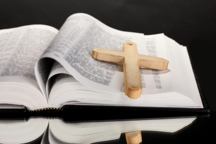 Open bible with wooden cross on page.