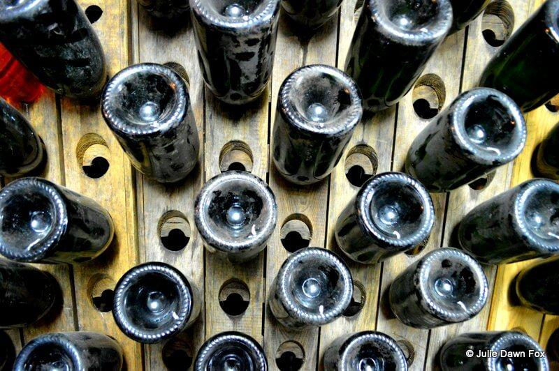 Wooden riddling rack for turning bottles by hand to clear the cloudiness in the wine.
