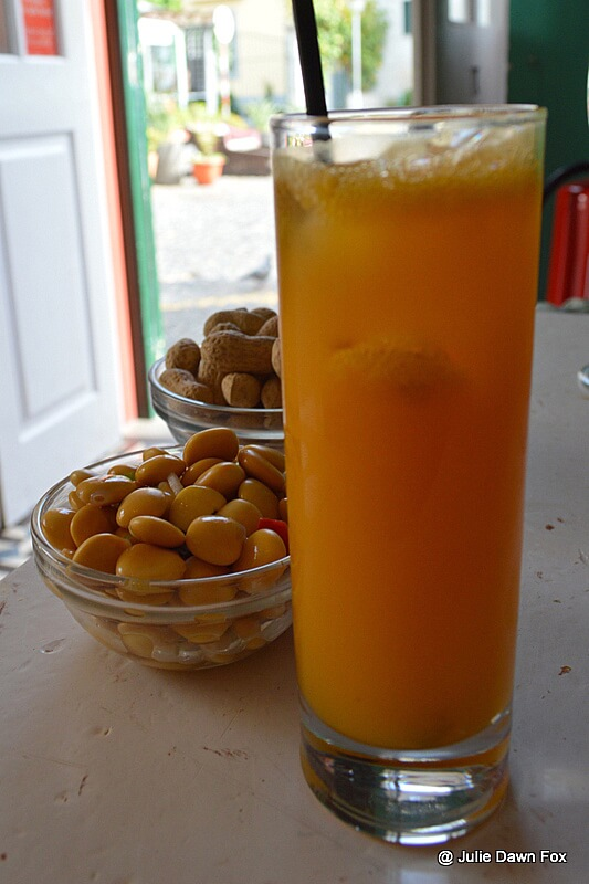 Long tall glass of Poncha served with lupin beans and peanuts