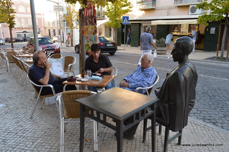 Sculpture of local poet, António Aleixo next to an outdoor table in Loulé, Algarve, Portugal. Photography by Julie Dawn Fox