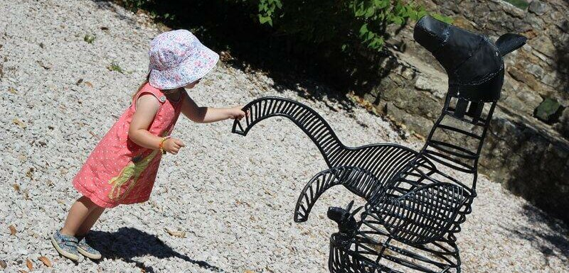 Young girl playing with sculptures at Penela Castle. Things to do with kids in Portugal