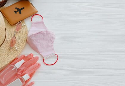 Safe travel in summer 2020. Pink face mask, gloves, antiseptic and disinfectant, passport, sunglasses,straw hat on white background. Copy space. Coronavirus vacation protection measures