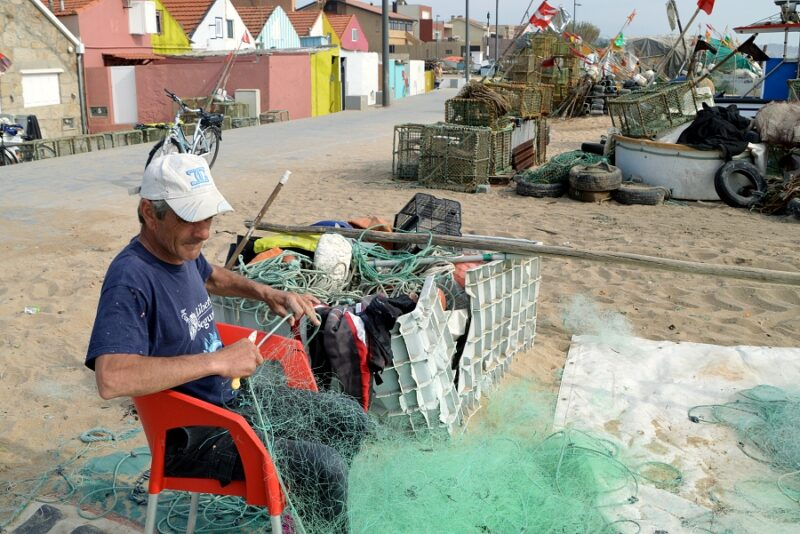 Fisherman mending his nets. Angeiras, northern Portugal