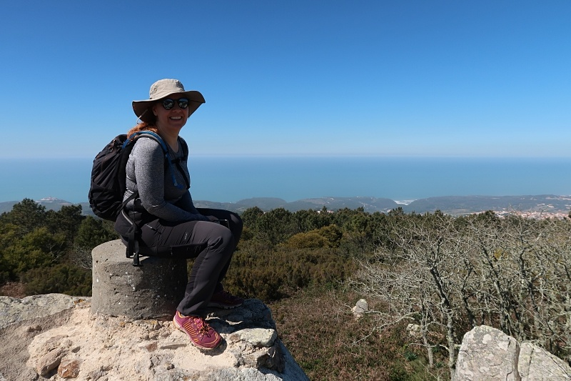 Female hiker sitting at the top of a hill in Sintra-Cascais Natural Park