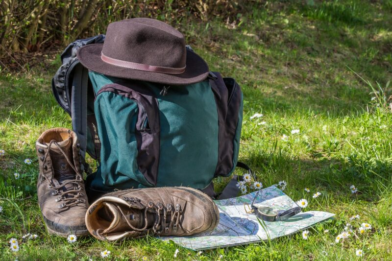 Backpack, hiking boots, hat, map and compass
