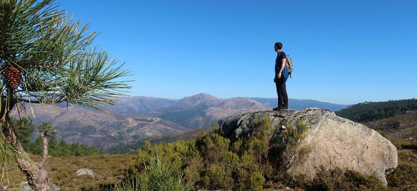 Man on a rock gazing at mountains on a Portugal hiking trail in Peneda-Gerês National Park