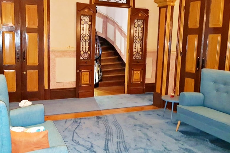 Hallway leading to ornate staircase in Your Opo Bolhao Apartments Porto.