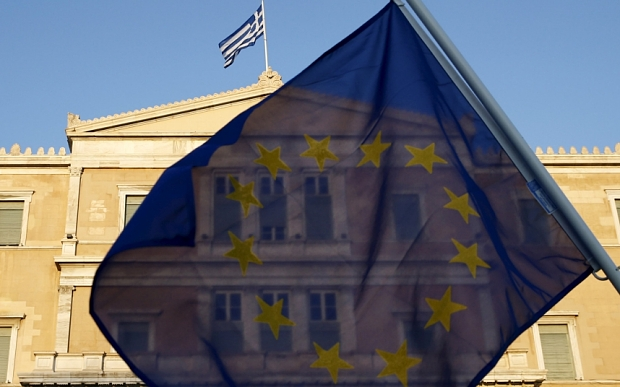 A protester waves an EU flag at the entrance of the Greek parliament, during a rally calling on the government to clinch a deal with its international creditors and secure Greece's future in the Eurozone, in Athens June 18, 2015. Hopes of a breakthrough at Thursday's gathering of European finance ministers, once seen as the last opportunity for an agreement, looked increasingly remote. REUTERS/Yannis Behrakis
