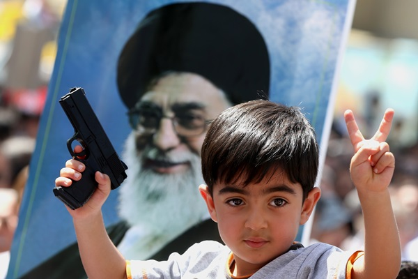 An Iraqi boy living in Iran holds a toy gun and flashes a victory sign in front of a poster of the Iranian Supreme leader Ayatollah Ali Khamenei in a demonstration against Sunni militants of the al-Qaida-inspired Islamic State of Iraq and the Levant, or ISIL, and to support the Grand Ayatollah Ali al-Sistani, Iraq's top Shiite cleric, in Tehran, Iran, Friday, June 20, 2014. (AP Photo/Ebrahim Noroozi)