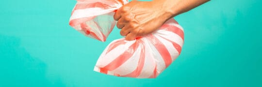 Image of hand grabbing plastic bag —bringing flexi back to be recycled