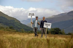 Company Founders holding placards in field to promote new BrewDog Forest.