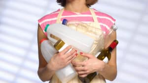 Person clutching empty recyclable plastic and glass bottles.