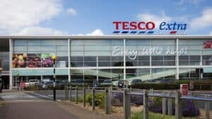 """""""Altrincham, UK - July 7, 2012: Tesco Supermarket sign, logo and slogan on the store in Altrincham, Cheshire, UK. Tesco is a multinational retailer of groceries and general goods, and is based in the UK. They are the second-largest retailer in the world measured by profits. Tesco Extra stores are larger hypermarkets selling a wide range of goods."""""""