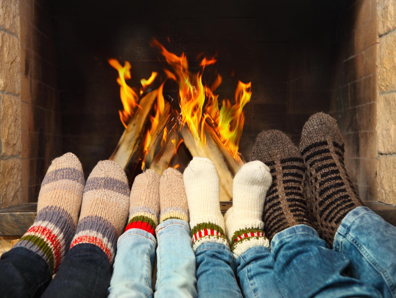 Feets of a family wearing woolen socks warming near the fireplace