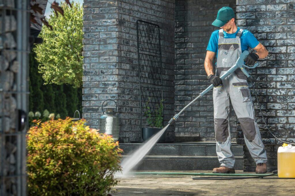 Driveway Pressure Washing. Caucasian Worker Cleaning Area in Front of the House.  \How to Save Money on Exterior Cleaning