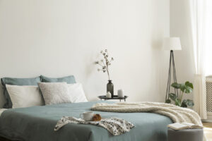 Revamping Your Bedroom in 2021: Where to Save and Where to Splurge  Bedroom interior with sage green and white sheets and cushions and a blanket. Black metal table with vases beside the bed. A lamp standing in the corner. Real photo.