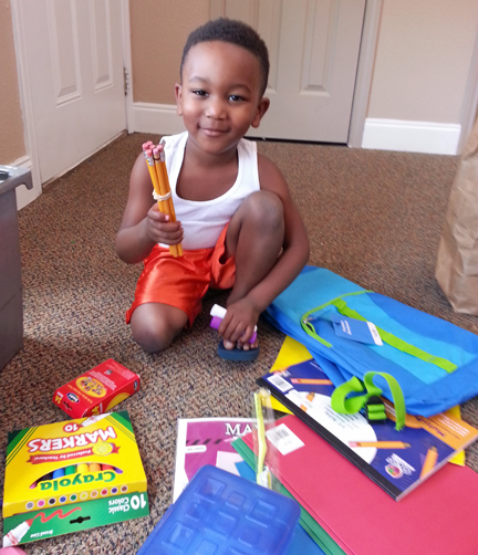 A young student receives school supplies from your gifts to and through Mission Arlington!