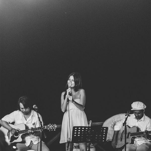 Guest performer singing with Bali Wedding Band at an intimate wedding reception on Keramas Beach, Bali