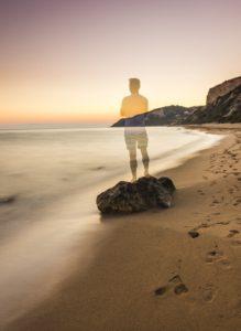 TRansparent man standing infront of beach comtemplating himself