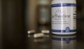 Bottle of L theanine supplement with capsules next to it