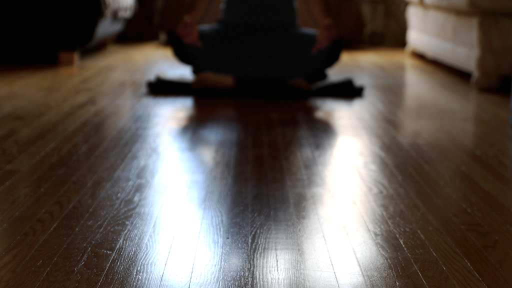 John Francisco sitting in daily meditation practice on a cushion casting a shadow over the illuminated hardwood floor