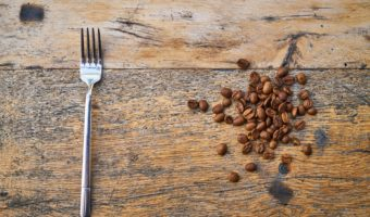 Overhead view of fork next to coffee beans on empty table