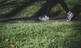 Woman walking for weight loss through the parking with running shoes over the grass