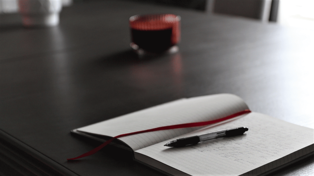 Open journal with a pen next to a red ribbon divider on a grey table. The open pages filled with goals to achieve for the year.