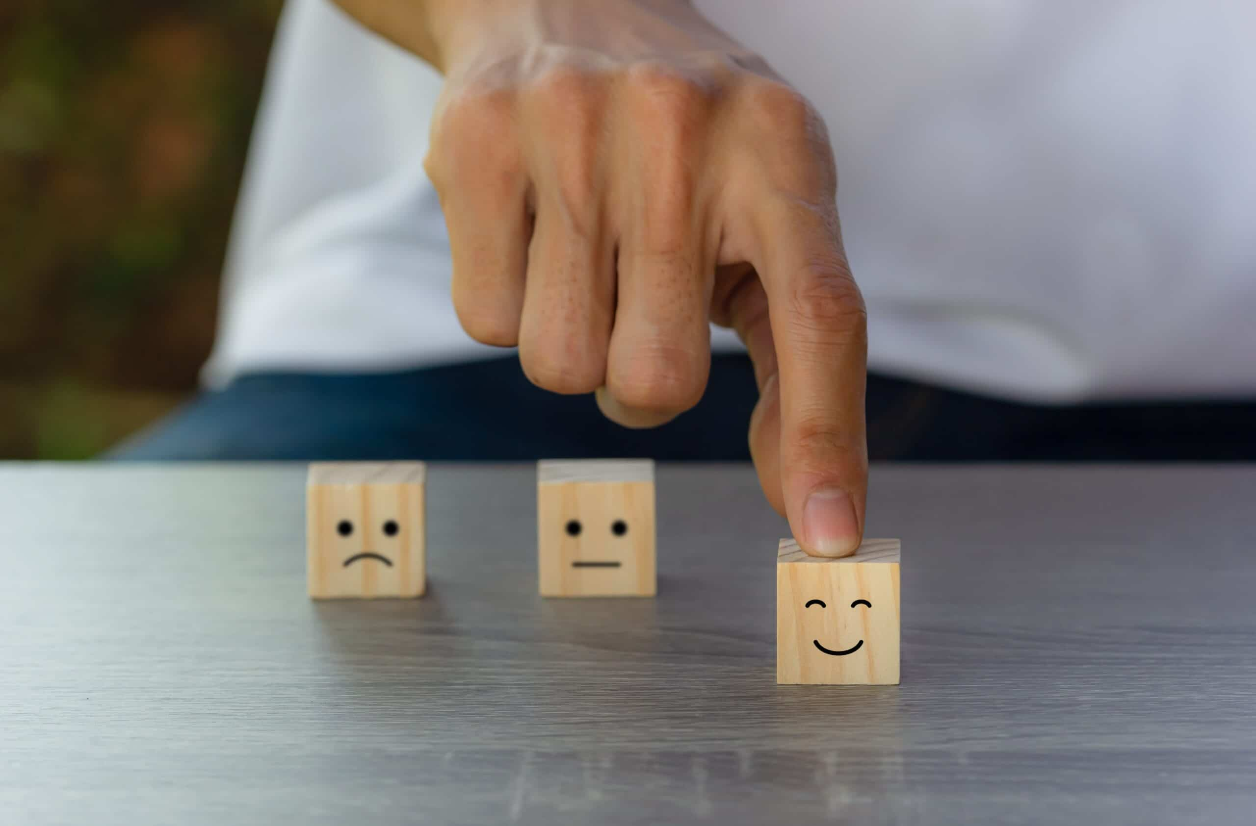 Conceptual the customer responded to the survey. The client using hand choose happy face smile icon on wood block. Depicts that customer is very satisfied. Service experience and satisfaction concept.