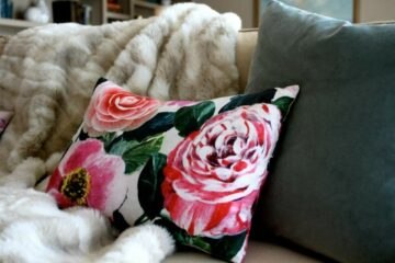 Colleen Dawson of Raye Design created this pink floral lumbar pillow, shown on a sofa with a faux fur throw blanket and slate throw pillow - custom pillows fabricated by Pillows by Dezign, a custom decorative pillow fabricator for hospitality, commercial and residential interior design projects.