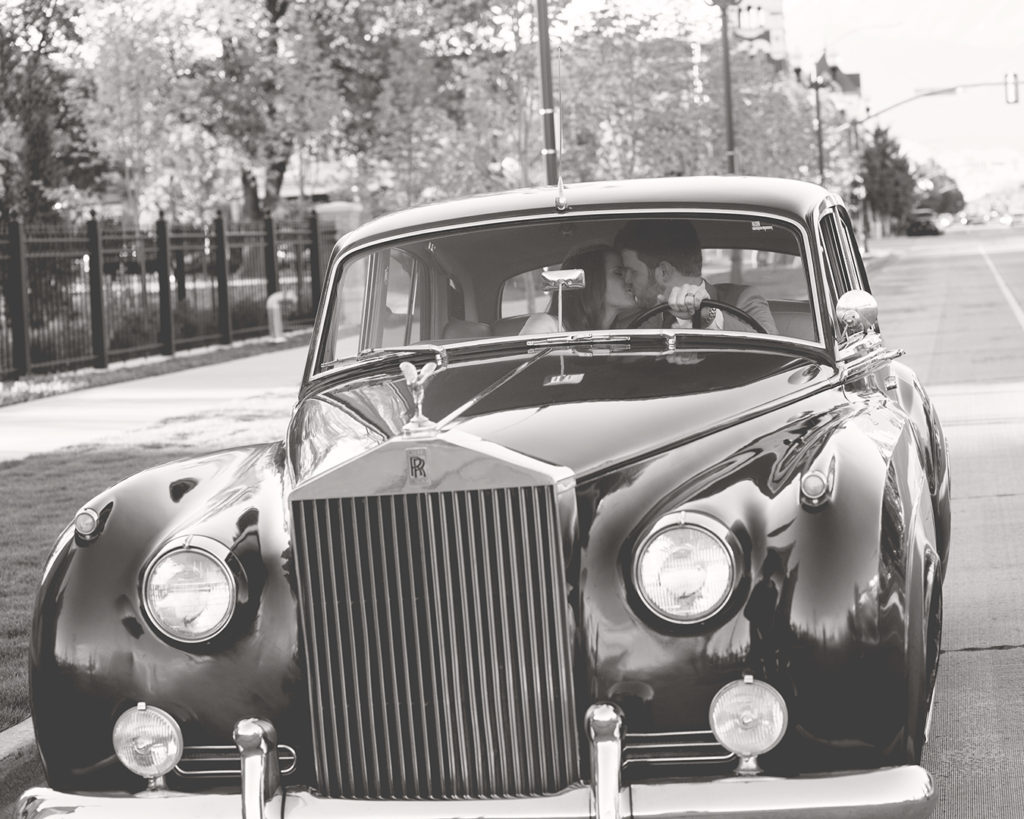 Bride and Groom kissing in Rolls Royce black and white