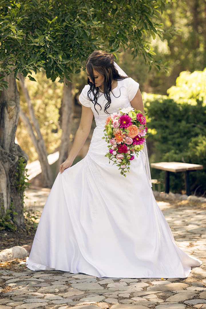 Bride holding dress with bouquet