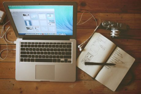 laptop and notebook with pen sitting on desk