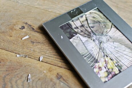 wedding picture in frame with smashed glass broken to pieces symbolizing divorce