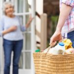 cleaning lady with supplies visiting senior woman at home