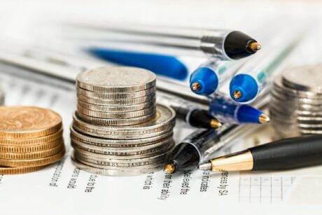 money coins and pens sitting on graphed sheet