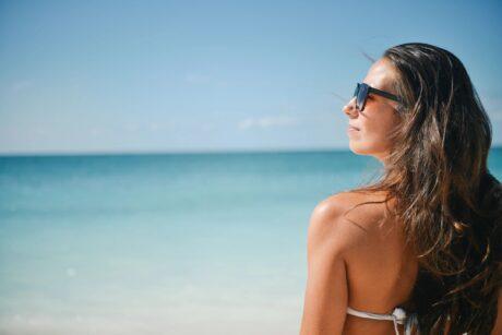 woman sitting on beach wearing sunglasses enjoying sun