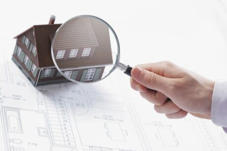 hand holding magnifying glass inspecting a house