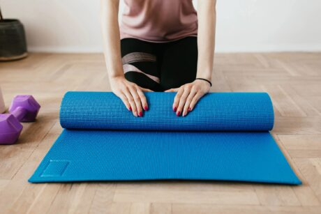 woman rolling up a blue yoga mat