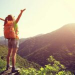 woman with arms in air enjoying the sunshine or outdoors standing in valley