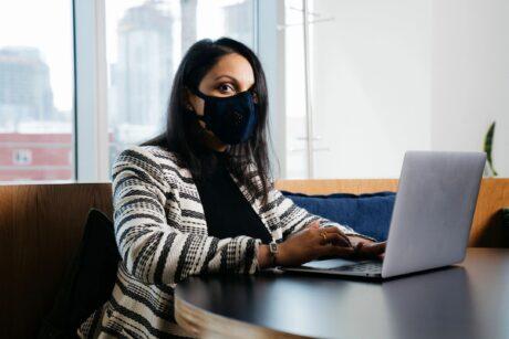 woman wearing mask sitting at desk working on laptop