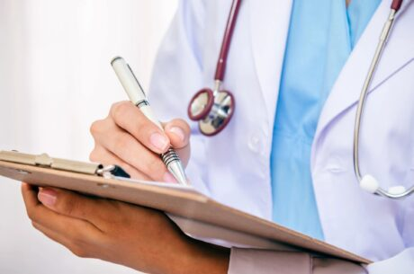 healthcare provider holding data board wearing medical clothes and stethoscope