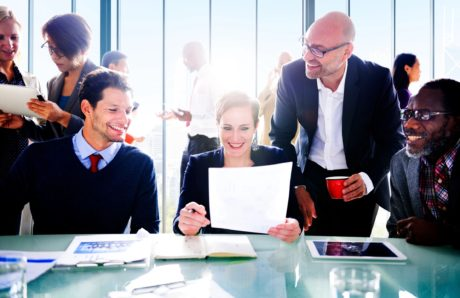 female ceo sitting a table showing business papers to two men