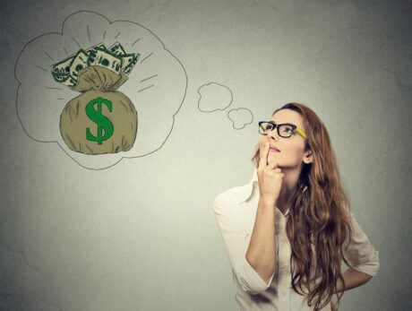 woman wearing eyeglasses thinking about money, with dollar sign on bag full of money inside thought bubble