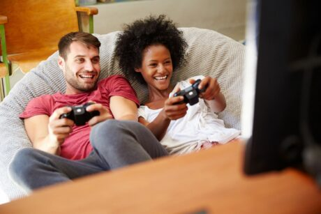 man and woman on sofa laughing and holding gaming controllers