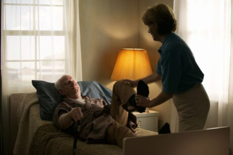 senior man lying in bed being assisted by younger woman bending knee as exercise