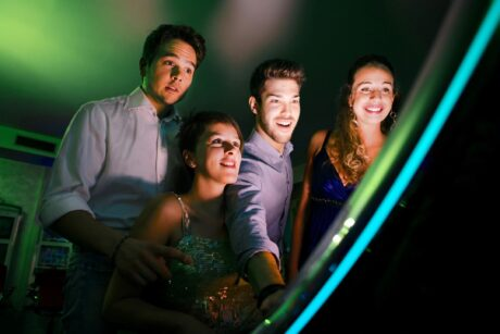 two couples laughing while playing games watching a games screen