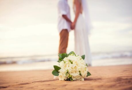 bride and groom holding hands on beach with bouquet of white flowers in front of them on beach