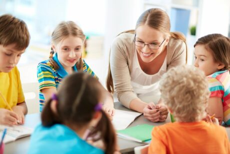 daycare woman in glasses leans over table with children sitting all around smiling